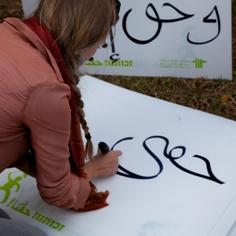 """אישה כותבת על שלט את המילה """"זכותי"""" בערבית. צילום: תום רביב"""
