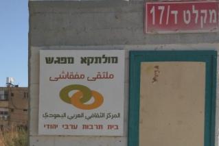 תמונת המקלט עם שלט בעברית ובערבית: מולקתא-מפגש - בית תרבות ערבי יהודי