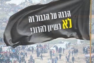 דגל שחור ועליו הכיתוב: הגנה על הגבול זה לא רישיון להרוג!