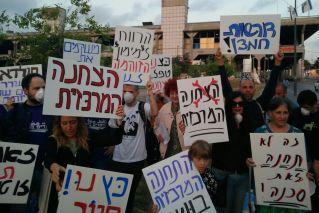 """מפגינים נגד התחנה המרכזית נושאים שלטים: """"הצחנה המרכזית"""", """"זה לא תחנה זאת סכנה"""", """"הרווח למימון הזוהמה לנו"""""""